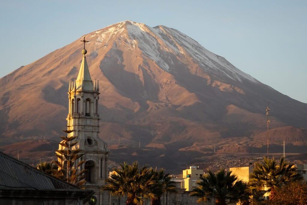 Kirchturm vor einem Berg
